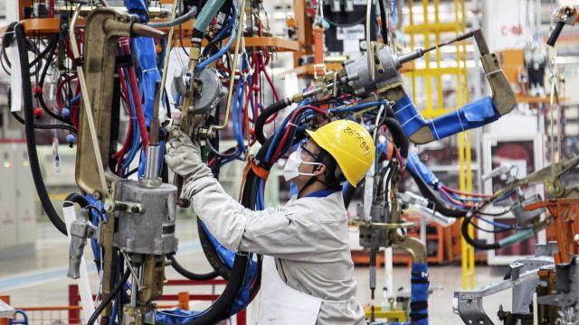 рабочий в каске производит ремонт оборудования